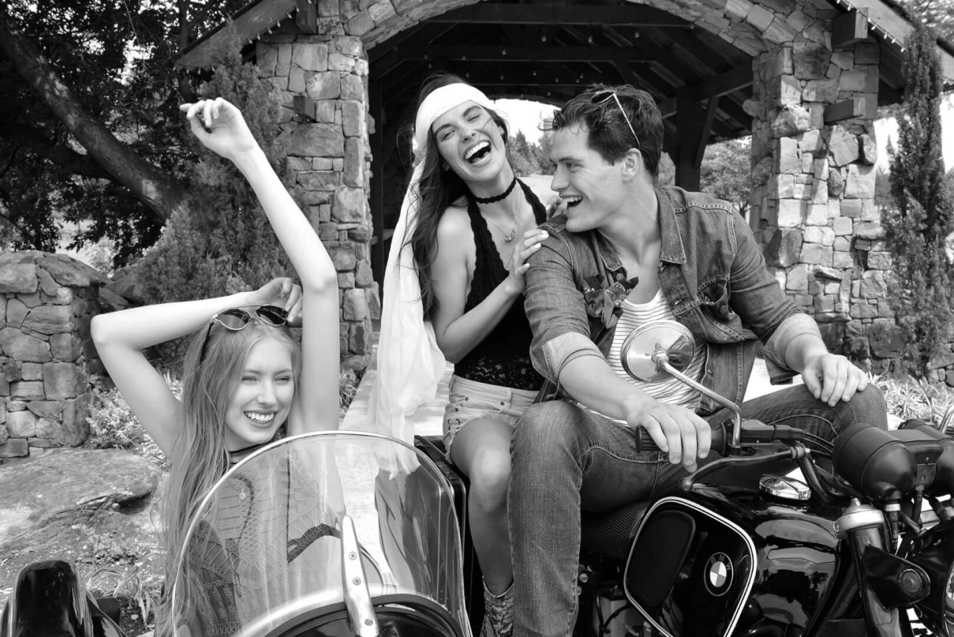 beautiful young people laughing with vintage motorcycle in black and white