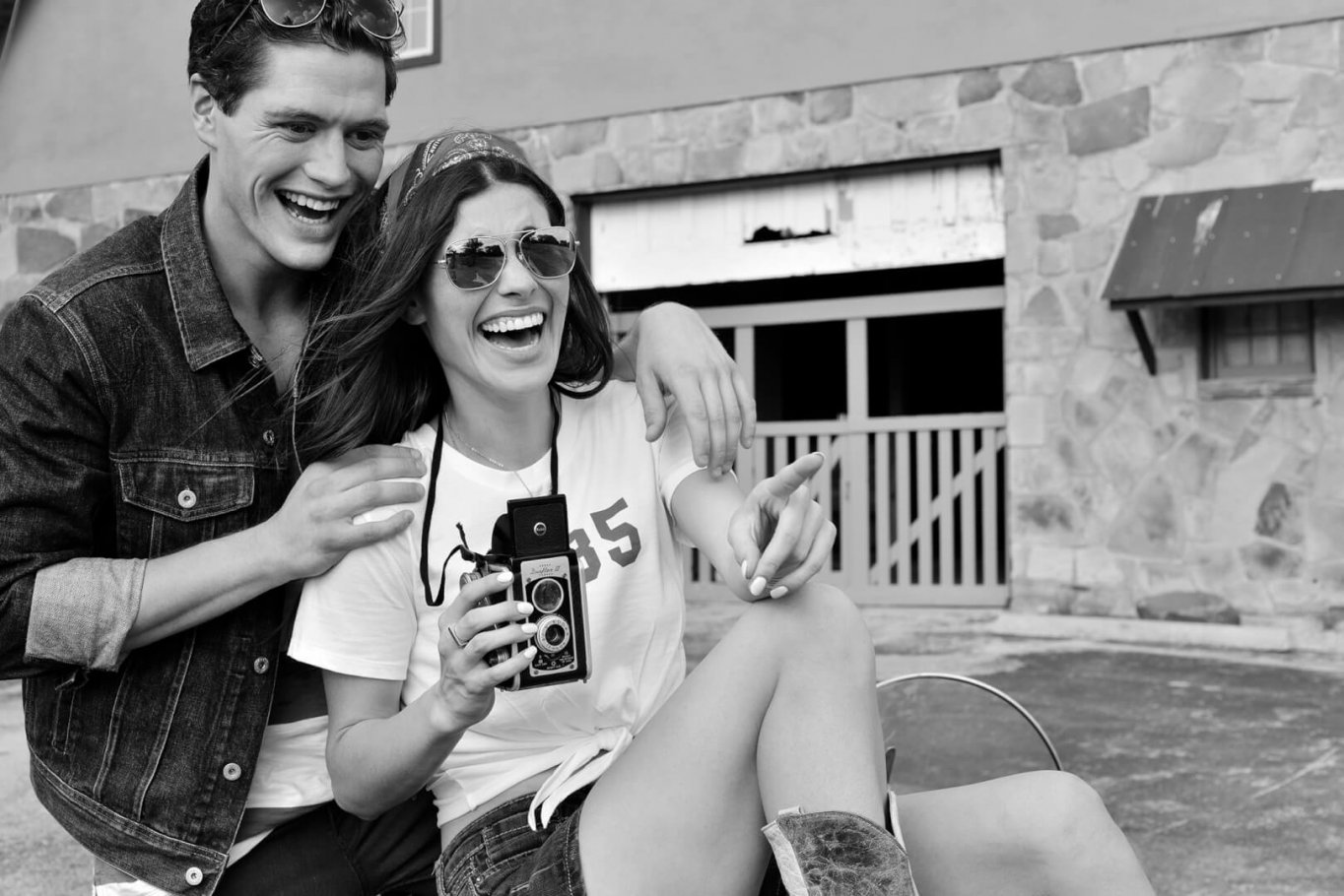 beautiful couple with vintage camera laughing