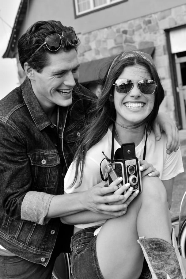 beautiful young couple with vintage camera laughing in black and white